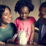Young family teaching with young daughter holding a jar full of money